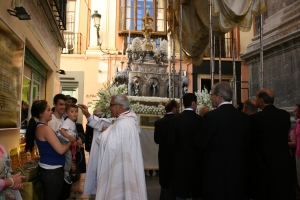 Mons. Martínez bendice a un niño durante la procesión.